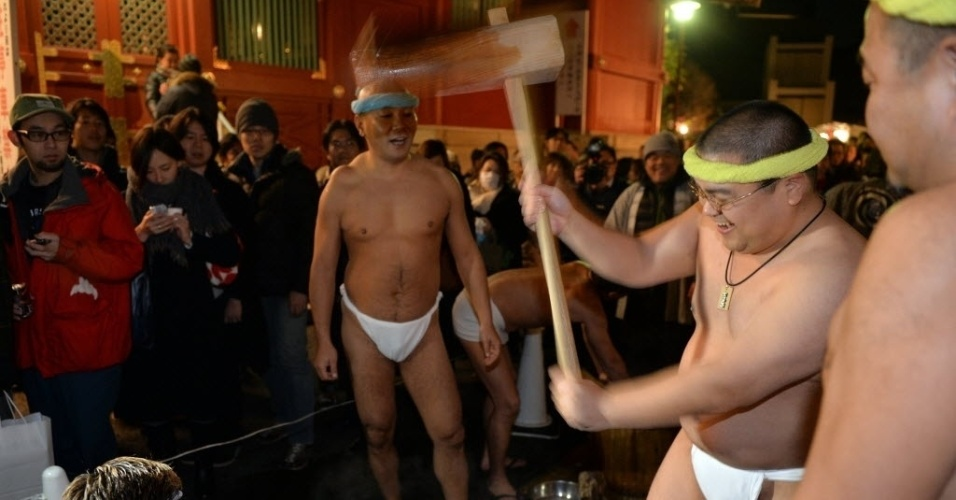 1°.jan.2014 - Em Tóquio (Japão), homens seminus amassam arroz a ser cozido durante celebração do Ano-Novo