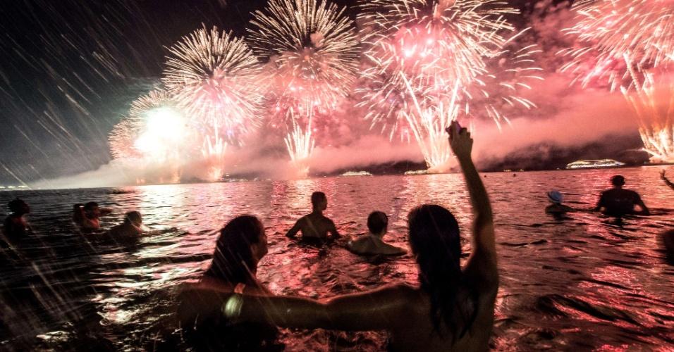 1º.jan.2014 - Pessoas assistem à queima de fogos da praia de Copacabana, no Rio de Janeiro, de dentro do mar