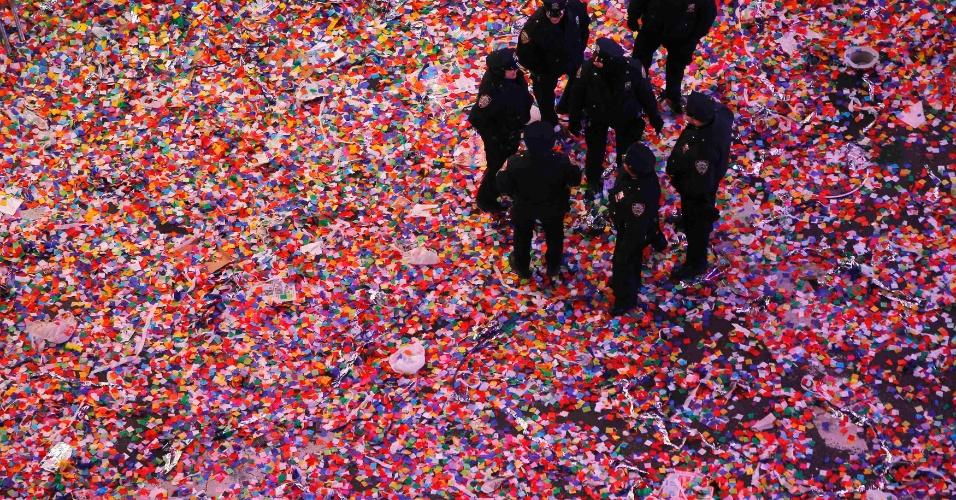 1º.jan.2014 - Policiais conversam sobre 'tapete' de confete, depois da festa de Réveillon da Times Square, em Nova York