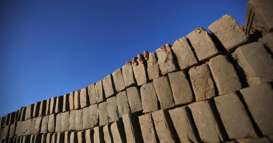 2.jan.2013 - Rahul Maji, 12, segura uma pilha de tijolos enquanto trabalha em uma fábrica, onde também vive com sua família, em Katmandu, no Nepal, nesta quinta-feira (2). Um grupo de jovens nepaleses associados com uma organização sem fins lucrativos, chamada Gothalo Nepal, tomou a iniciativa de prover educação básica a crianças pertencentes a famílias carentes uma vez por semana, nesta fábrica de tijolos