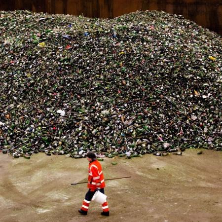 Homem caminha ao lado de uma enorme pilha de garrafas em um centro de reciclagem de vidro - Robin Van Lonkhuijsen/AFP