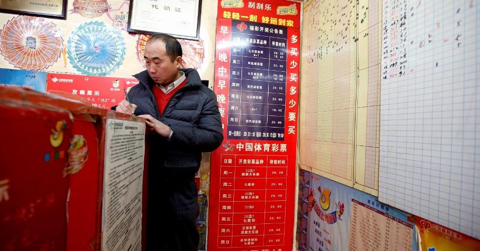 6.jan.2014 - Chinês preenche jogo para loteria em Xangai. Após distribuir U$ 23 bilhões (cerca de R$ 55 bilhões) em 2012, perdendo apenas para a norte-americana, que distribuiu U$ 37 bilhões (aprox. R$ 88 bilhões) no mesmo período, estima-se que a loteria chinesa ultrapasse a americana até 2015, passando a ser aquela com a maior distribuição de prêmios do mundo