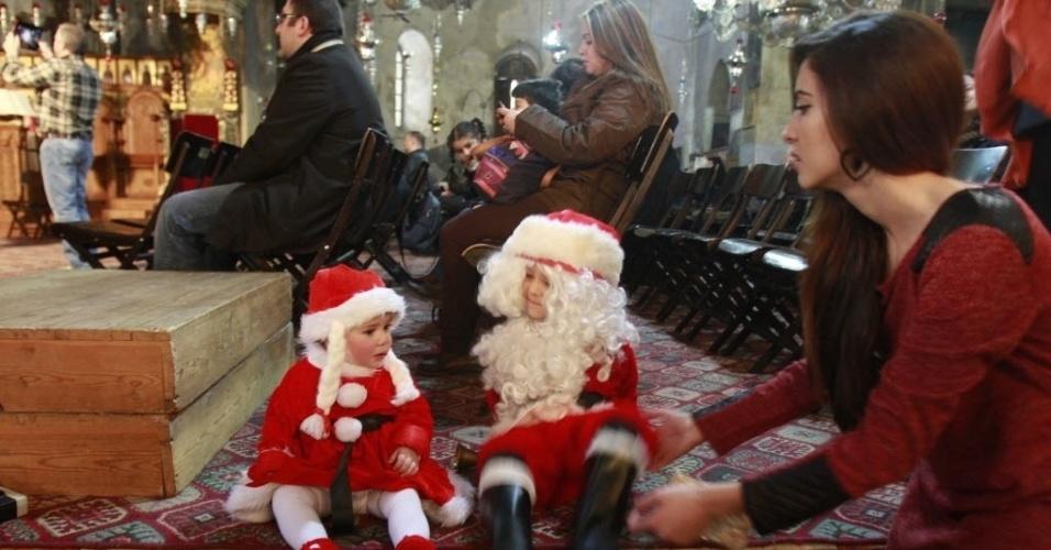 6.jan.2014 - Crianças cristãs palestinas, vestidas como Papai Noel sentam em frente à igreja da Natividade, aceito pelos cristãos como o lugar do nascimento de Jesus Cristo, na cidade de Belém, na Cisjordânia. Os cristãos ortodoxos se preparam para celebrar o Natal nesta terça-feira (7)