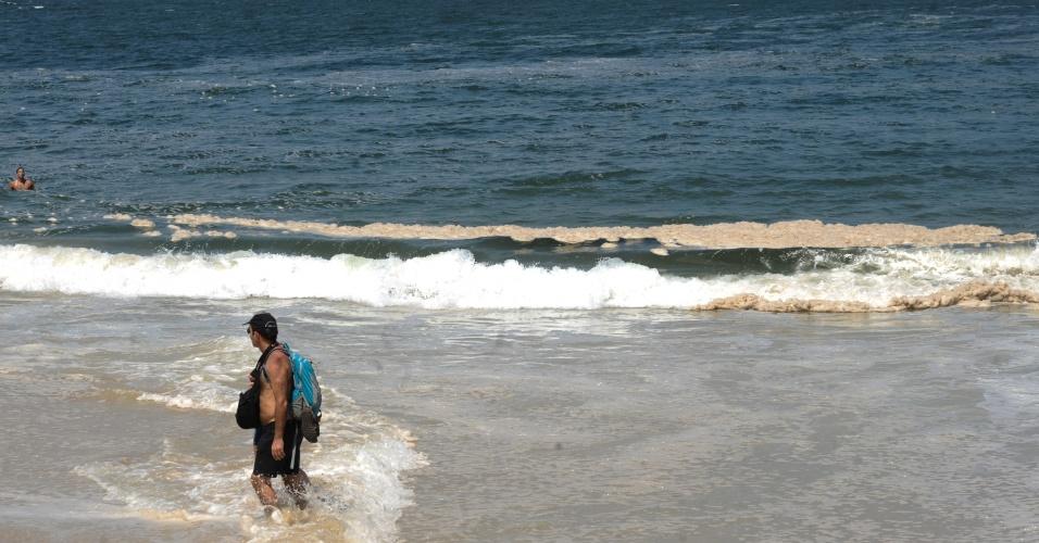 6.jan.2014 - Homem observa a espuma amarelada que apareceu pela manhã em praias das zonas oeste e sul do Rio. Segundo o Instituto Estadual do Ambiente (Inea), o fenômeno é comum no verão e resulta da decomposição de algas