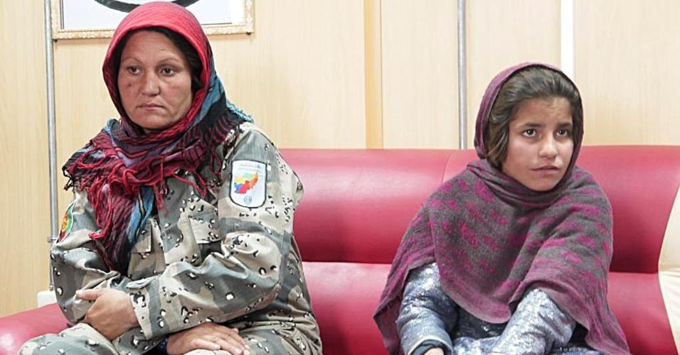 6.jan.2014 - Sphozmay, 10, se senta próximo a uma policial na província de Hellman, no Afeganistão, em foto divulgada nesta segunda-feira (6). A menina seria usada pelo Talibã em um atentado suicida