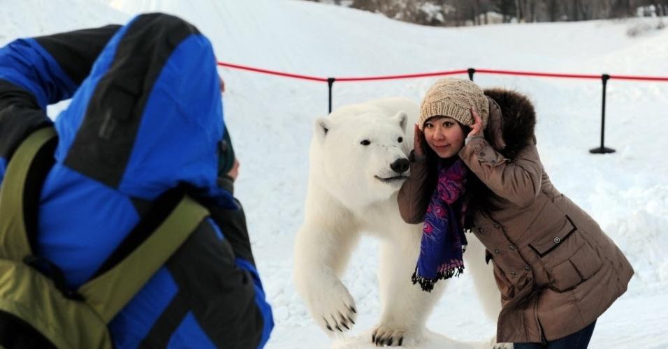 6.jan.2014 - Uma mulher posa para foto ao lado de um urso polar de pelúcia, em exposição na International Snow Sculpture Expo, em Harbin, capital da província de Heilongjiang, no nordeste da China, nesta segunda-feira (6)