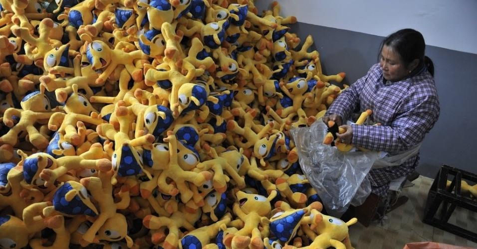 6.jan.2014 - Uma trabalhadora chinesa dá os últimos retoques aos bonecos do mascote da Copa do Mundo do Brasil 2014, o Fuleco, em uma fábrica na cidade de Tianchang, na província de Anhui, na China. A fábrica recebeu um pedido de mais de um milhão de bonecos que serão distribuídos em todo mundo