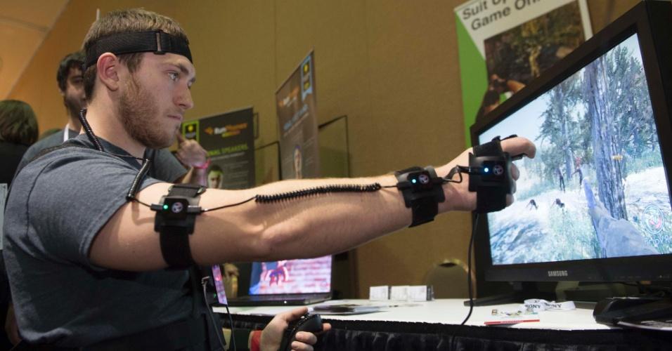 Chris Jorge, da companhia EI Technology, joga um game com o Prio VR, um acessório de realidade virtual. Para funcionar, o usuário deve vestir sensores nos braços, no peito, na cabeça e ainda segurar um controle em uma das mãos. Com ele, é possível, por exemplo, jogar games em primeira pessoa e usar o braço como arma para atirar