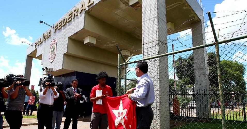 7.jan.2014 - Militantes do PT prestam apoio com bandeiras e palavras de ordem contra o julgamento do mensalão, na porta da superintendência da PF em Brasília, onde é aguardada a prisão do deputado João Paulo Cunha, condenado no processo