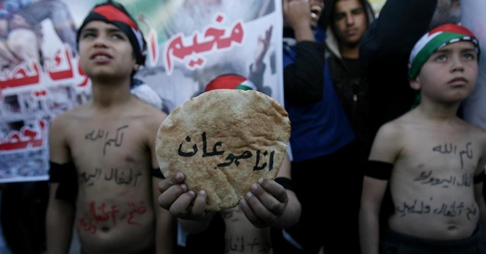 8.jan.2014 - Crianças palestinas participaram nesta quarta-feira (8) de uma manifestação em solidariedade aos refugiados palestinos do acampamento Yarmouk, em Damasco, Síria. Trinta deles morreram nos últimos três meses por inanição e doenças, agravadas pela piora na situação do país natal