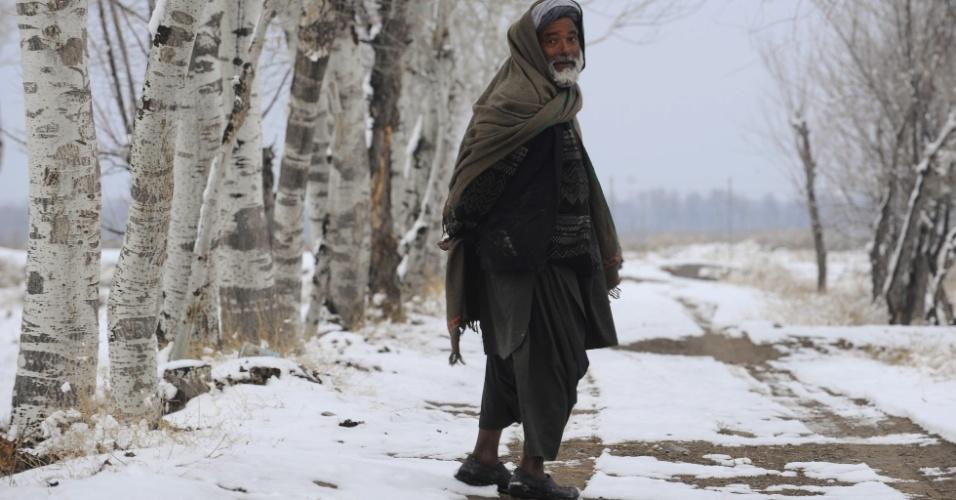 8.jan.2014 - Homem afegão caminha por estrada coberta de neve em Herat. Com o inverno se intensificando na Ásia Central, muitos afegãos lutam para dar abrigo adequado às suas famílias