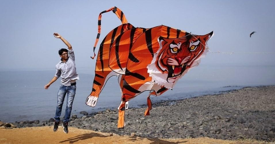 8.jan.2014 - Homem pula ao lado de uma enorme pipa com formato de tigre durante o Festival Internacional de Kite em Mumbai, Índia