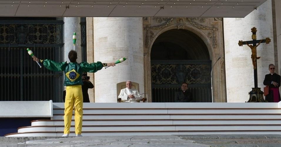8.jan.2014 - Papa Francisco assite enquanto um malabarista vestido com a estampa da bandeira do Brasil se apresenta na praça de São Pedro, no Vaticano