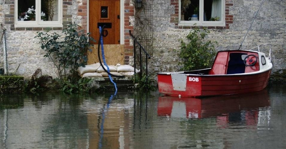 8.jan.2014 - Um barco flutua em frente a uma casa durante inundação em Bury perto de Pulborough, no sul da Inglaterra. Temporais tem atingido o Reino Unido desde o começo deste mês. A Agência para o Meio Ambiente advertiu que ondas gigantes podem provocar mais inundações nas regiões costeiras