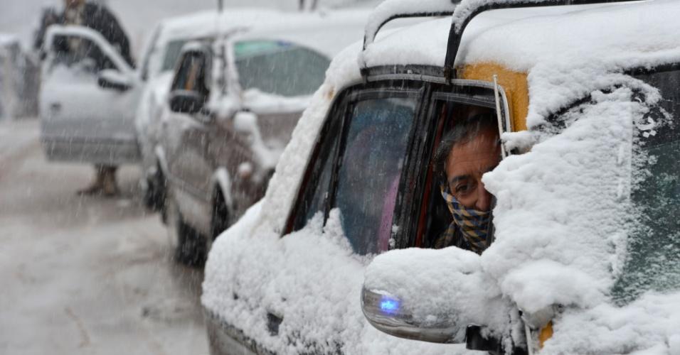 8.jan.2014 - Um motorista de táxi paquistanês dirige seu veiculo durante uma nevasca, a 70 quilômetros de Islamabad, nesta quarta-feira (8). A primeira neve da temporada caiu em Murree e nas áreas adjacentes