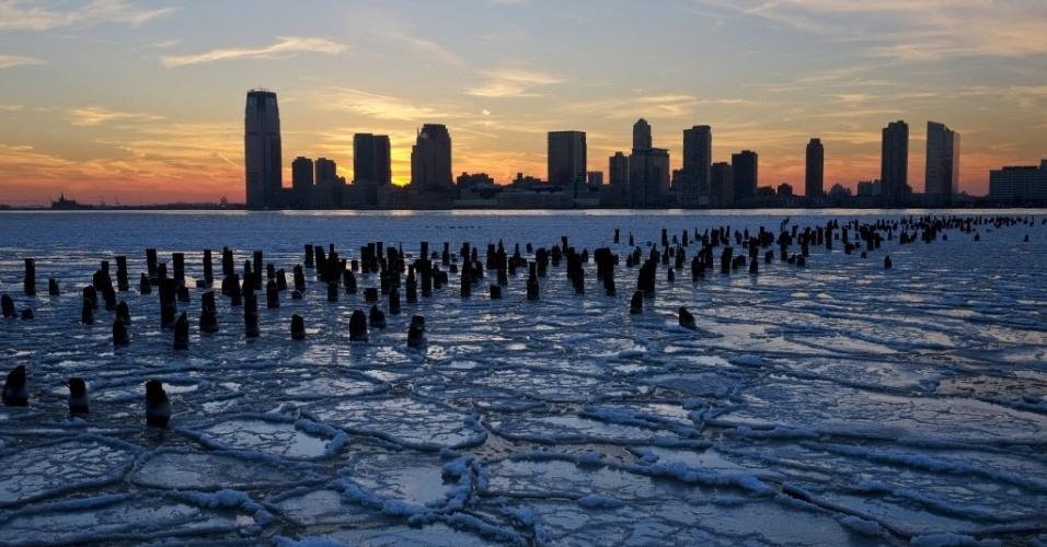 9.jan.2014 - Blocos de gelo flutuam no rio Hudson tendo a orla de Nova Jersey como plano de fundo, durante o pôr do sol, nesta quinta-feira (9), na cidade de Nova York