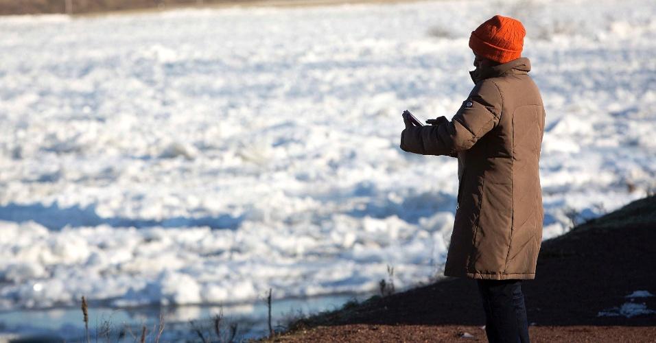 10.jan.2014 - Mulher mexe no celular às mergens do rio Delaware, Nova Jersey, nordeste dos EUA, nesta quinta-feira (9). Blocos de gelo emperram o rio, e o aumento da quantidade de gelo gera preocupação em relação a inundações na região