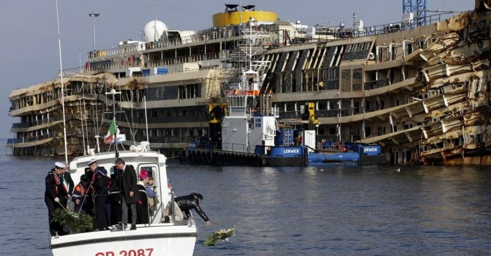 13.jan.2014 - Parente de vítima do naufrágio do Costa Concordia joga flores em frente ao navio no aniversário de dois anos da tragédia, próximo à ilha de Giglio, na Itália. 32 pessoas morreram no naufrágio