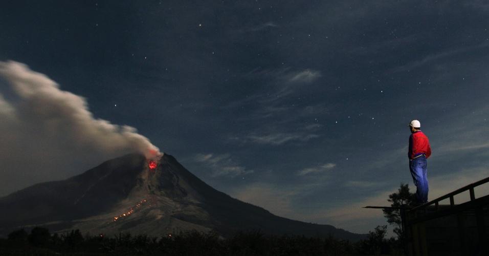 Um homem observa o vulcão Sinabung, que expele cinzas e lavas próximo ao vilarejo de Jraya, no distrito de Karo, em Sumatra, no norte da Indonésia, nesta segunda-feira (13). Mais de 25 mil pessoas precisaram ser evacuadas desde que as autoridades emitiram alerta máximo por causa do vulcão, em novembro de 2013
