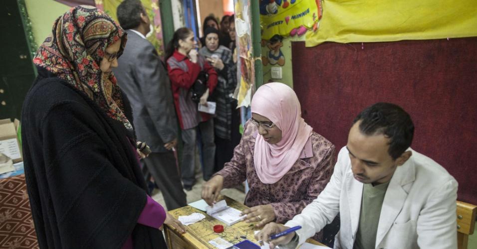 14.jan.2014 - Mulher egípcia deposita seu voto no referendo da nova Constituição do país. A votação vai durar dois dias e observadores acreditam que irá levar a uma vitória folgada do governo egípcio liderado pelos militares que depuseram o ex-presidente Mohammed Mursi, em julho de 2012. Os militares fizeram uma forte campanha para incentivar os egípcios a participarem da votação