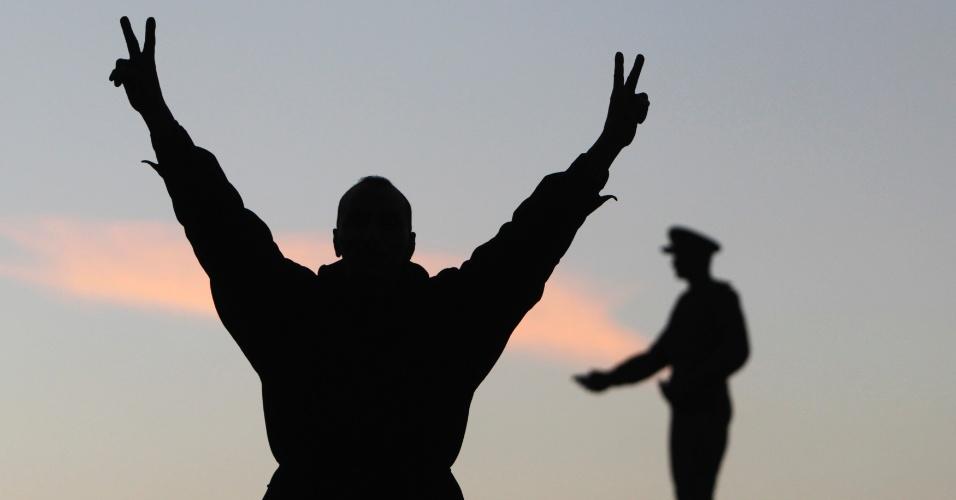 15.jan.2014 - Egípcio faz sinal da vitória diante da estátia do ex-chefe das Forças Armadas Staff Abdel Moneim Riad próximo à praça Tahrir, durante o segundo dia de votação no referendo para a nova Cosntituição do país