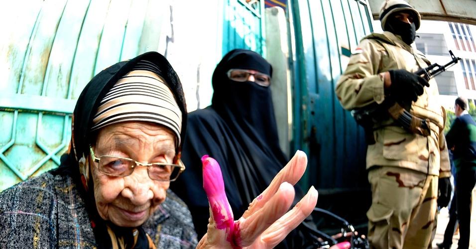 15.jan.2014 - Mulher egípcia mostra o dedo marcado por tinta vermelha após votar no segundo dia de referendo para a nova Constituição, na cidade de Alexandria