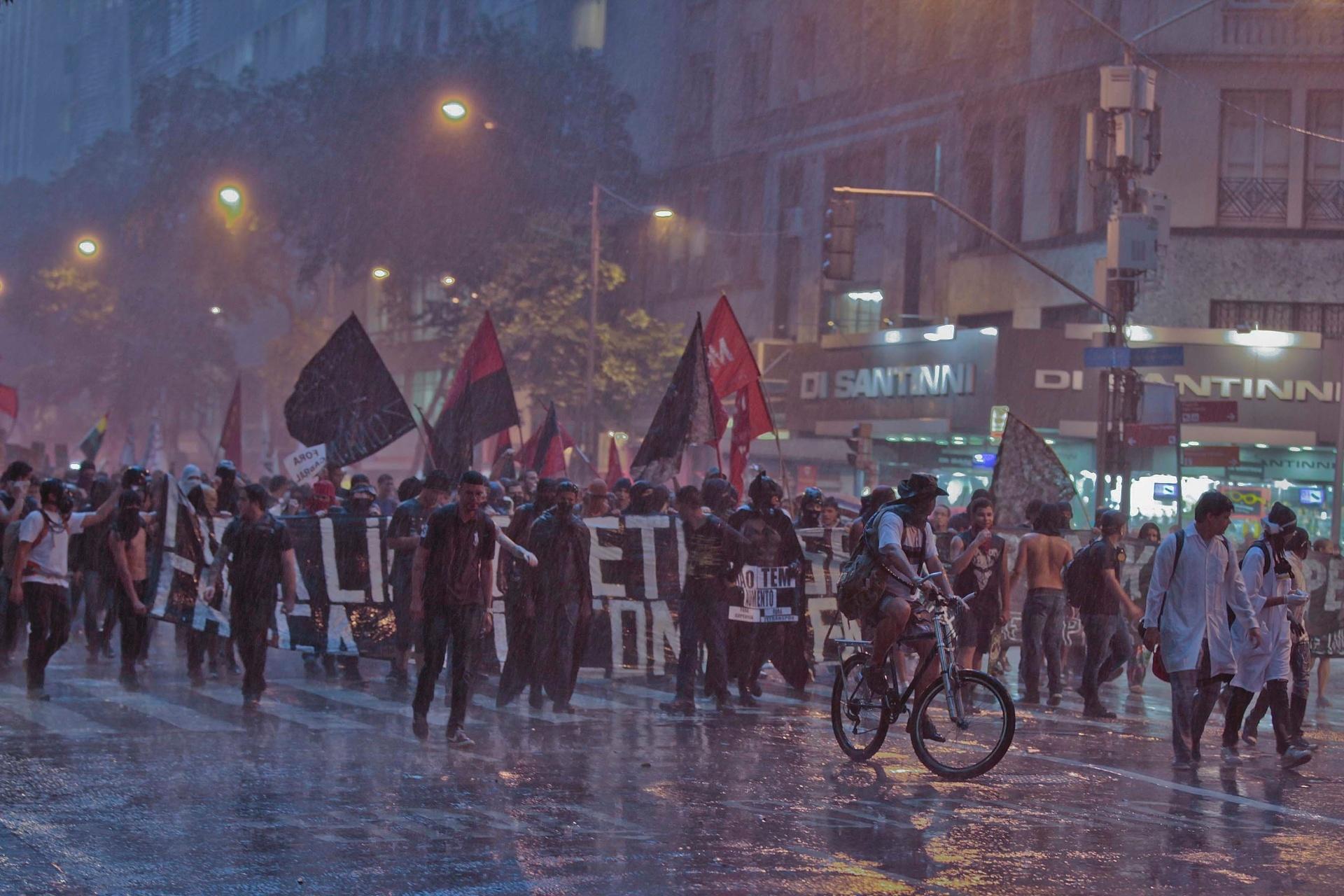 16.jan.2014 - Mesmo sob forte chuva, manifestantes protestam contra o aumento das passagens do transporte público na capital fluminense, no centro do Rio, nesta quinta-feira (16). Eles se reuniram na praça localizada atrás da Igreja da Candelária, acompanhados por dezenas de policiais militares