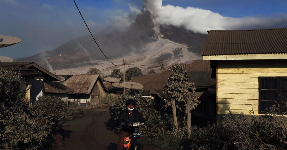 17.jan.2014 - Morador circula de motocicleta por vilarejo de Beras Tepu, aos pés do monte Sinabung, após chegar de abrigo temporário, nesta sexta-feira (17). Mais de 26 mil moradores foram evacuados desde que as autoridades elevaram o status de alerta para o vulcão para o nível mais alto, em novembro de 2013