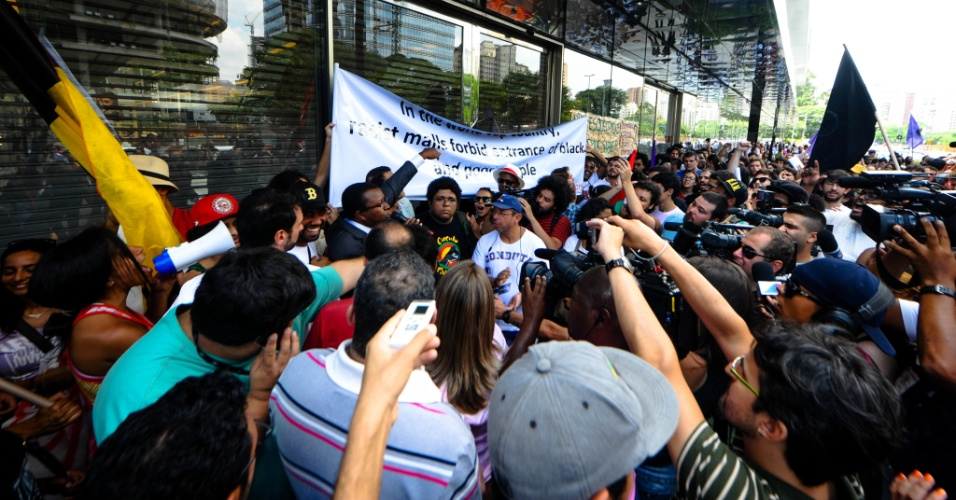 """18.jan.2014 - Integrantes de movimentos sociais protestam em frente ao Shopping JK Iguatemi, na zona oeste de São Paulo neste sábado. O evento foi intitulado """"Rolé contra o racismo"""". O Shopping fechou as portas durante o protesto. No cartaz carregado pelos manifestantes, está escrito, em inglês: """"No país da Copa do Mundo, shoppings racistas proíbem a entrada de negros e pobres"""""""