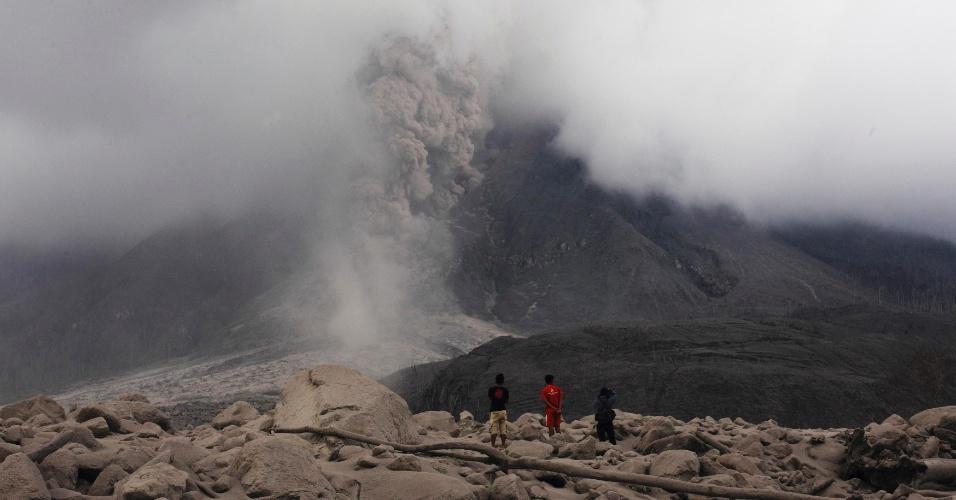 19.jan.2014 - Jovens observam o vulcão Sinabung expelir cinzas e fumaça próximo ao vilarejo de Sigarang Garang, no distrito do Karo, no norte de Sumatra, na Indonésia, neste domingo (19). Mais de 26 mil pessoas precisaram deixar suas casas desde a emissão do alerta de erupção por parte das autoridades