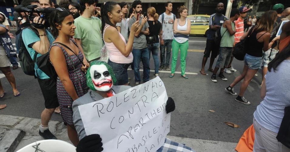 19.jan.2014 - Manifestante fantasiado de Coringa segura cartaz em frente ao shopping Leblon, na zona sul do Rio de Janeiro, em protesto contra o impedimento da realização de rolezinhos dentro desse tipo estabelecimento comercial. O shopping foi fechado neste domingo (19), por causa do movimento
