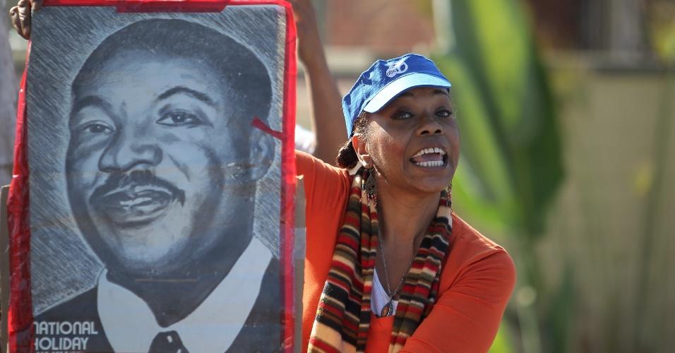 20.jan.2014 - A americana Tommie Johnson segura retrato de Martin Luther King Jr durante a parada anual em Los Angeles, na California. A parada é uma homenagem ao defensor dos direitos civis e coincide com o feriado comemorado nesta segunda-feira (20)
