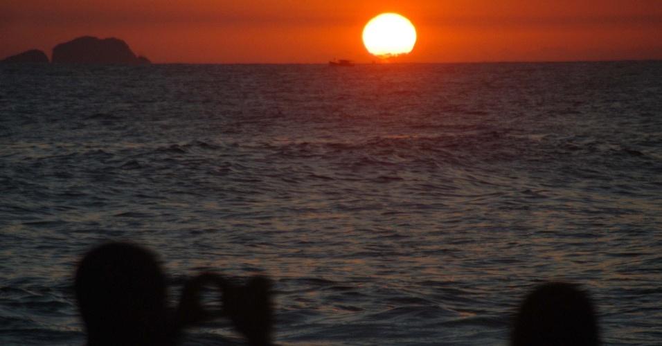 20.jan.2014 - Banhistas observam o pôr do sol na praia de Ipanema, nesta segunda-feira (20). A temperatura ficou acima de 30 graus e devido ao feriado de São Sebastião, as praias ficaram lotadas no Rio de Janeiro