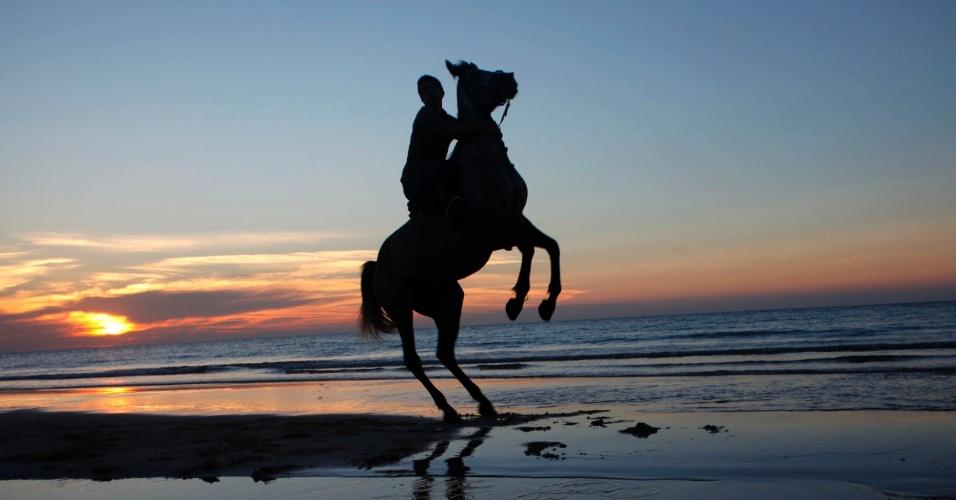 20.jan.2014 - Garoto palestino monta a cavalo durante o pôr-do-sol na faixa de Gaza