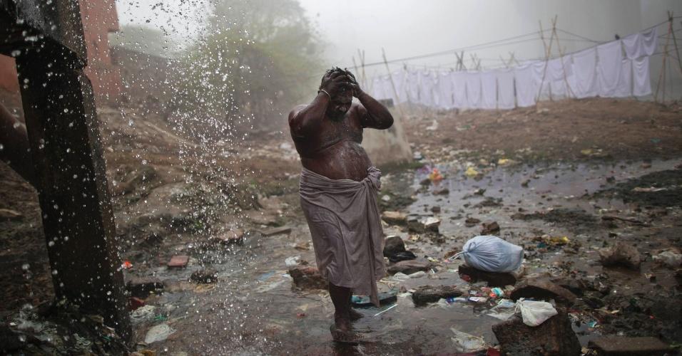 20.jan.2014 - Homem toma banho utilizando a água de um cano quebrado durante uma fria manhã em Nova Déli, capital da Índia. De acordo com a ONU, apenas 34% da população total da Índia tem acesso à rede de água e esgoto