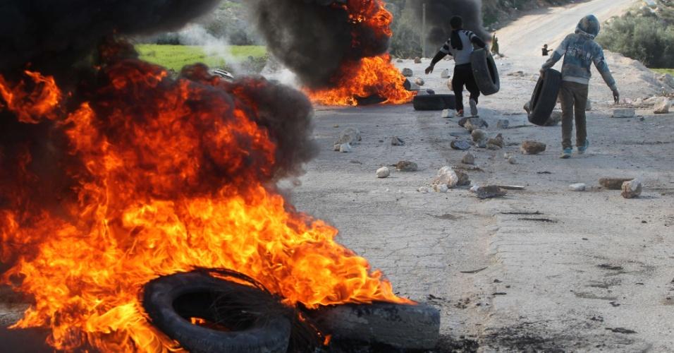 20.jan.2014 - Manifestantes palestinos carregam pneus durante mais um dia de confrontos com as forças de segurança de Israel. O protesto é contra a demolição de uma fábrica de móveis palestina construída sem permissão, segundo as autoridades israelenses