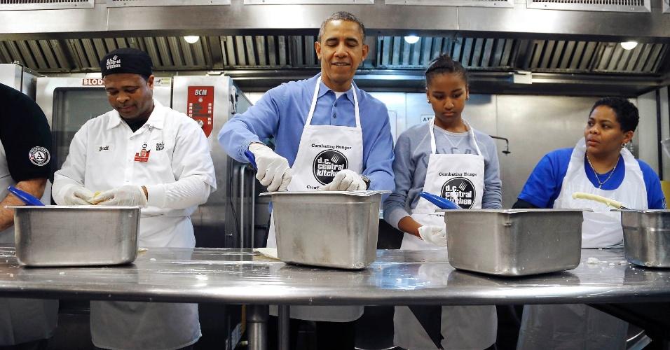 20.jan.2014 - O presidente americano Barack Obama e sua filha Sasha (segunda a partir da direita) recheiam burritos com voluntários da entidade beneficente Cozinha Central DC em homenagem ao ativista dos direitos civis Martin Luther King Jr nesta segunda-feira (20)