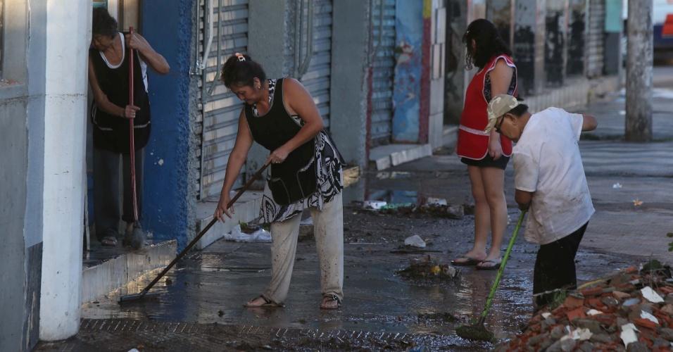 23.jan.2014 - Moradores limpam a calçada na rua Melvin Jones no centro de Osasco, em São Paulo, nesta quinta-feira (23). A chuva forte que atingiu São Paulo, entre a tarde e a noite de quarta-feira (22), provocou estragos na zona sul da capital e na Grande São Paulo