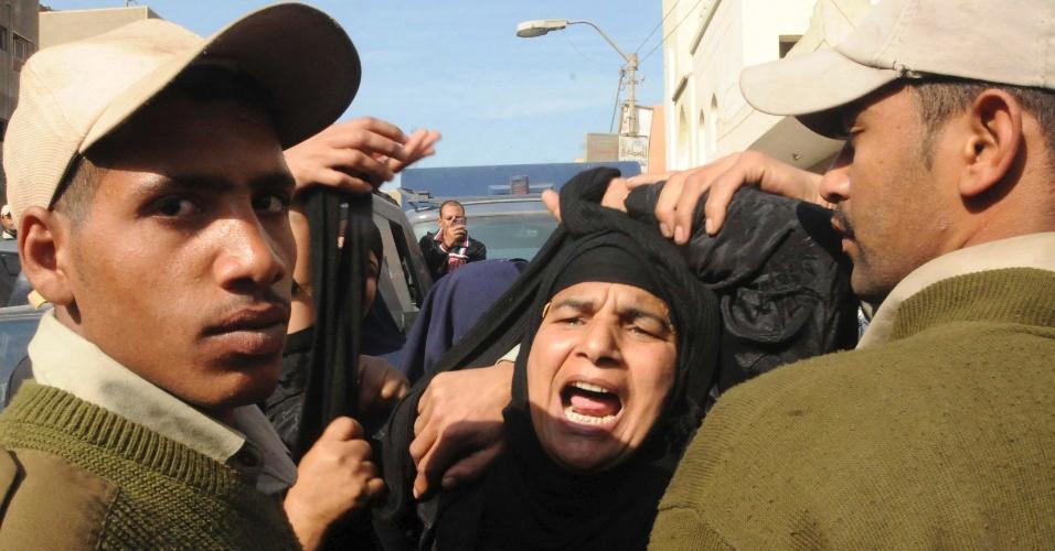 23.jan.2014 - Uma mulher grita palavras de ordem durante o funeral de cinco policiais mortos quando homens mascarados motorizados abriram fogo em um ponto de inspeção na província de Beni Suef, a 100 km ao sul do Cairo, no Egito, nesta quinta-feira (23)