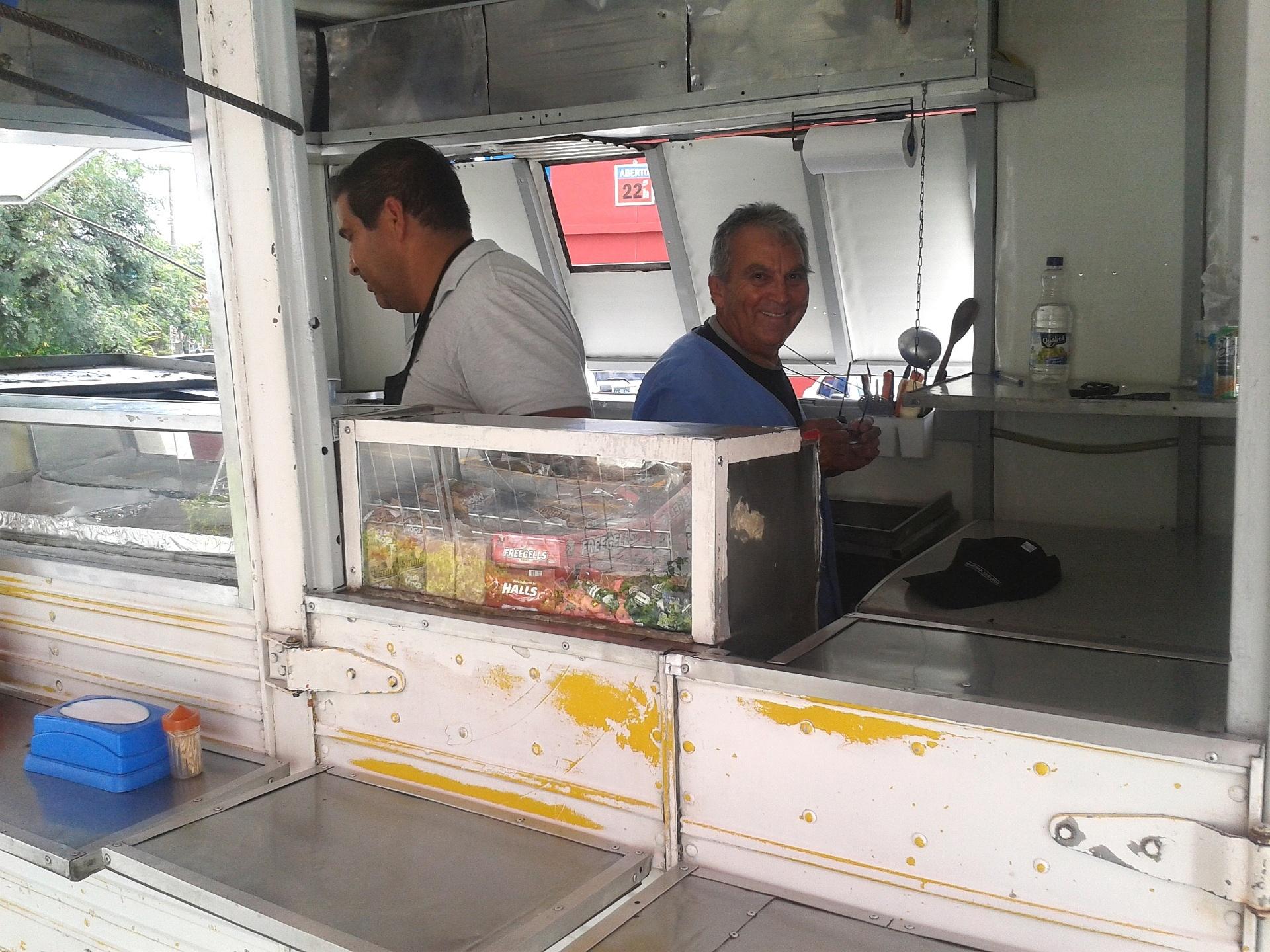 Wilson de Oliveira Botelho Júnior (de branco) e o pai (de azul) vendem hot dog em uma Kombi adaptada próxima à praça Panamericana, na zona oeste de São Paulo (SP)