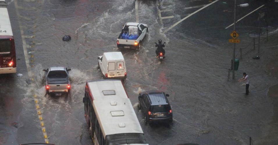 24.jan.2014 - Veículos trafegam por ponto de alagamento na avenida Nove de Julho, nas imediações da praça da Bandeira, sentido centro, durante forte chuva que atinge a capital paulista no fim da tarde desta sexta-feira (24)