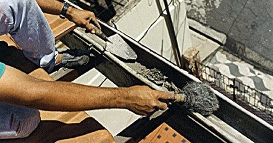 homem conserta calha de casa