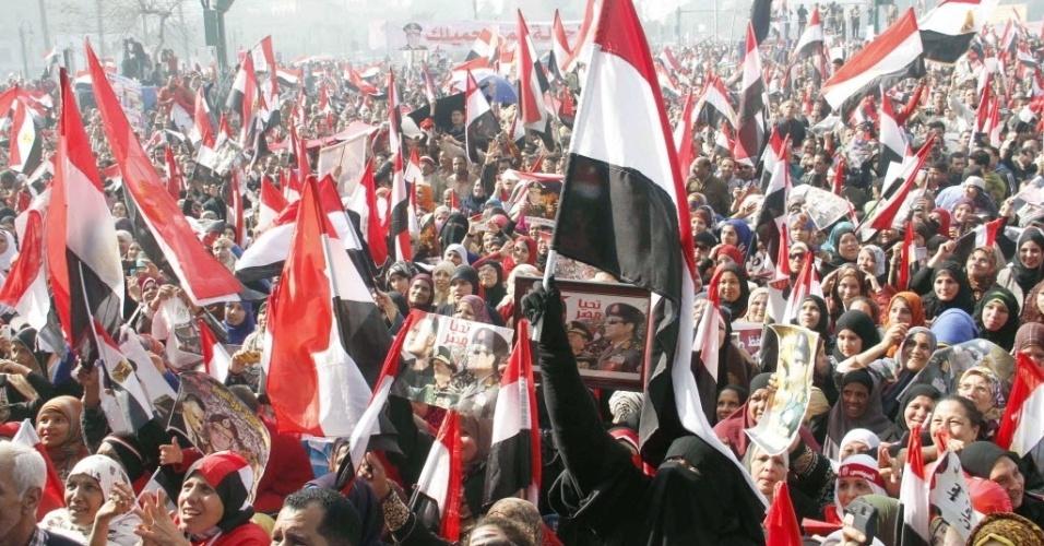 25.jan.2014 - Apoiadores do presidente interino do Egito, general Abdel Fatah al-Sisi, cantam e exibem cartazes em uma reunião na praça Tahrir, no Cairo. Pelo menos seis pessoas morreram durante os confrontos entre manifestantes favoráveis ao presidente deposto Mohamed Mursi e as forças de segurança egípcias neste sábado (25), data em que os egípcios comemoram os três anos do início da revolução que derrubou o ditador Hosni Mubarak