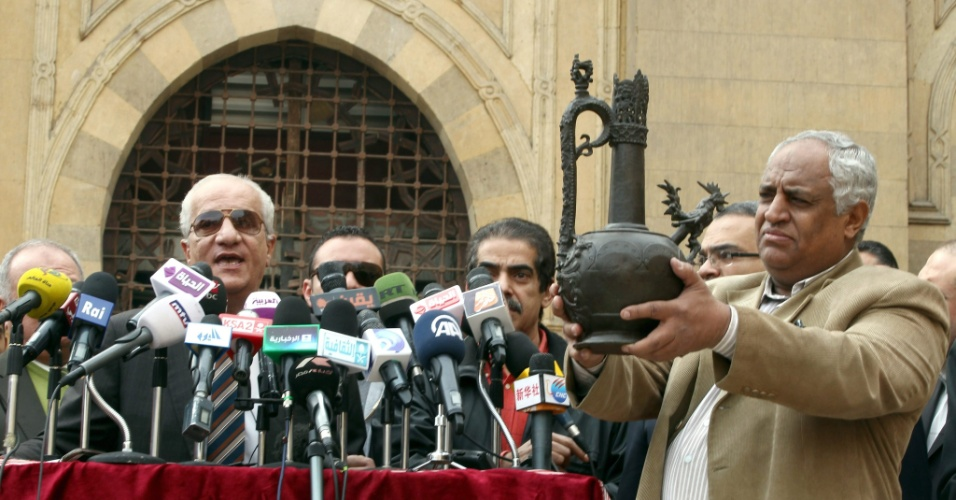 26.jan.2014 - Arqueólogo egípcio mostra o jarro de Marwan ibn Muhammad durante coletiva do ministro egípcio de Antiguidades, Mohamed Ibrahim (L), em frente ao Museu de Arte Islâmica, destruído por uma explosão de bomba na sexta-feira (24). Ibrahim negou relatos de que o jarro, uma das mais importantes peças exibidas no museu, foi roubados ou danificados no bombardeio. O jarro de bronze foi encontrado no túmulo de Marwan ibn Muhammad, que governou de Damasco até 750