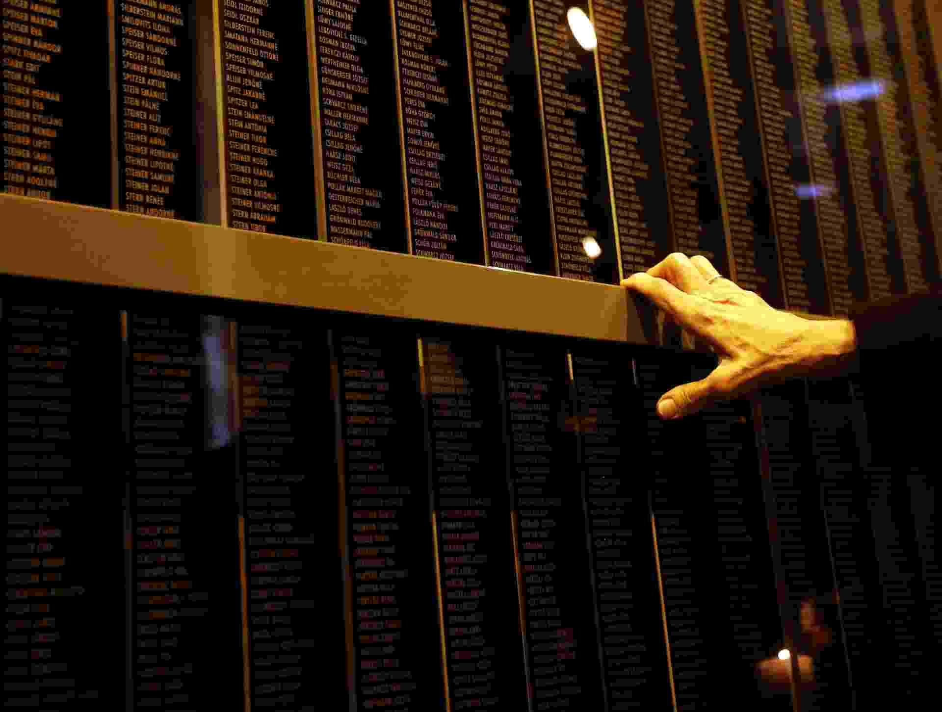 27.jan.2014 - Idoso toca o muro em que estão gravados os nomes das vítimas do regime nazista no Memorial do Holocausto de Budapeste, na Hungria. O dia da libertação do campo de concentração de Auschwitz lembra os seis milhões de judeus mortos no genocídio, sendo que mais de meio milhão eram húngaros - Laszlo Balogh/Reuters