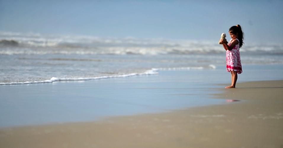 27.jan.2014 - Menina brinca com bicho de pelúcia enquanto aproveita o clima quente do litoral norte gaúcho. O verão deste ano no Rio Grande do Sul vem registrando temperaturas elevadas, frequentemente acima dos 30 graus Celsius