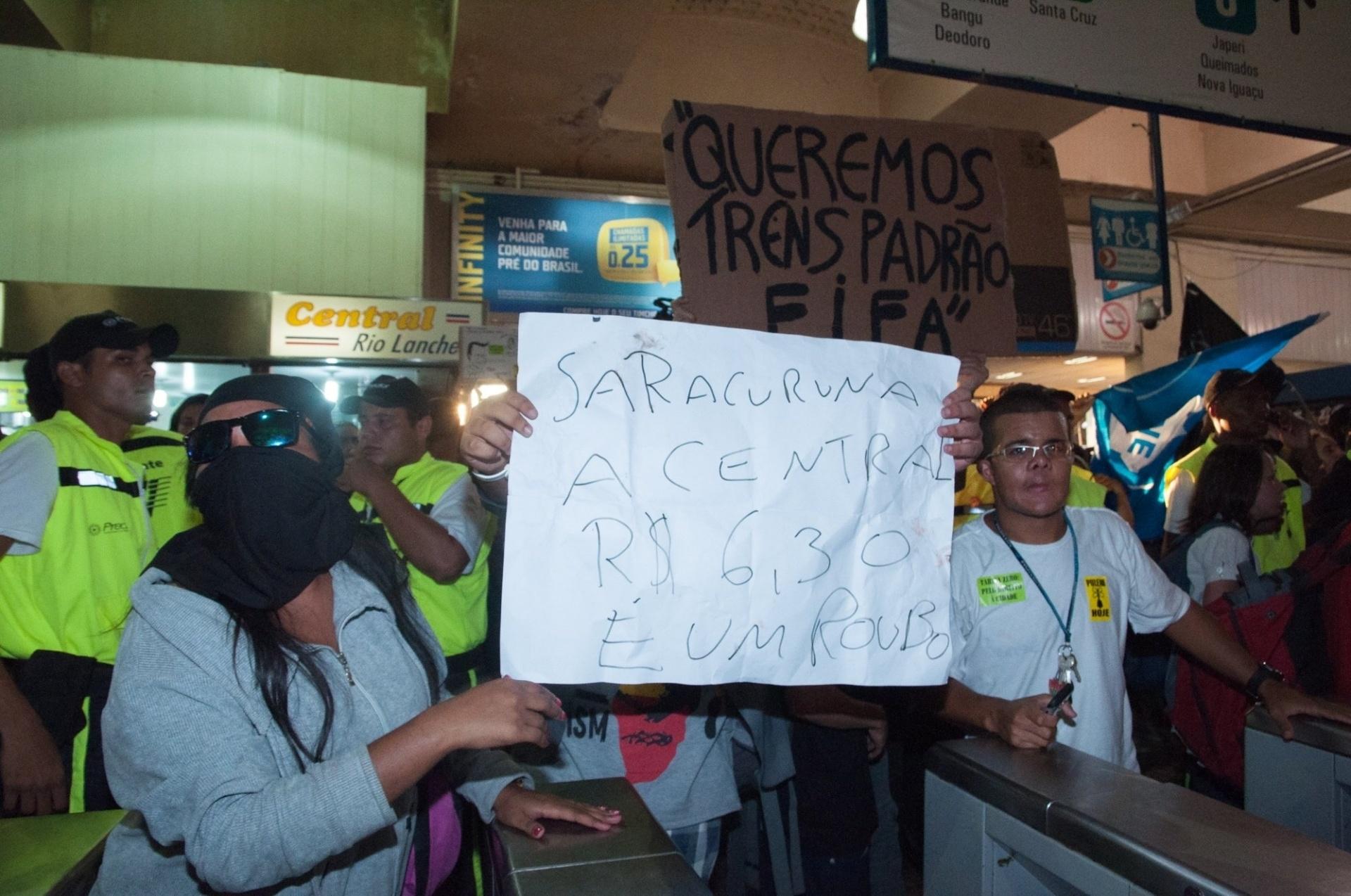 28.jan.2014 - Manifestantes seguram cartazes e tentam invadir a estação de trens da Central do Brasil, no centro do Rio de Janeiro, nesta terça-feira (28), pedindo para liberação das catracas. O protesto é contra o aumento da tarifa das passagens de ônibus e trens. Muitos trabalhadores se aproveitaram do ato e passaram sem pagar