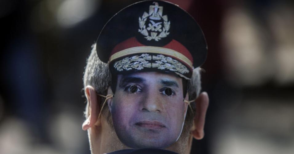 28.jan.2014 - Partidário usa máscara do chefe do exército do Egito, Abdel Fattah al-Sisi, candidato à presidência nas próximas eleições, no Cairo, onde começou nesta terça uma nova audiência do julgamento do presidente deposto Mohamed Morsi. Ele responde por fuga da prisão durante a revolução de 2011