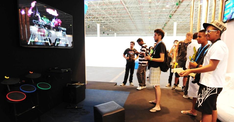 """Campuseiros participam de campeonato do jogo """"Guitar Hero"""" em estande do Banco do Brasil. Vencedor poderá dormir por uma noite em um quarto VIP com ar-condicionado, TV 3D, home theater, videogame, além de uma cama"""
