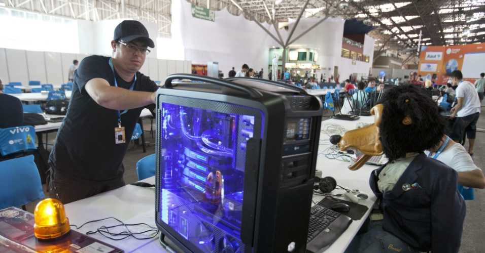 Participantes ficam reunidos em arena, onde estão localizados os cabos (para conexão de 40 Gbps), tomadas e bancadas. Muitos levam seus computadores modificados para o evento